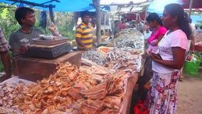 HIKKADUWA, SRI LANKA - FEBRUAR 2014: Lokale Mannverkauf und -frauen, die an Markt Hikkaduwa Sonntag, bekannt für seine breite Pal stock footage