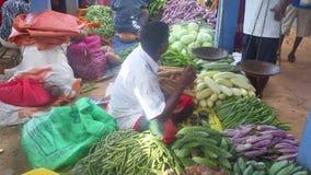 HIKKADUWA, SRI LANKA - FEBRUAR 2014: Lokaler Mann, der an Hikkaduwa-Markt sitzt und verkauft Markt Hikkaduwa Sonntag bekannt für  stock video