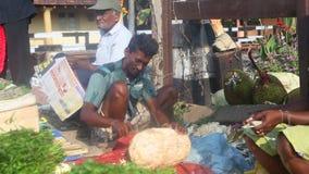 HIKKADUWA, SRI LANKA - FEBRUAR 2014: Lokaler Mannsitzen und -ausschnitt Jackfruit an Hikkaduwa-Markt Markt Hikkaduwa Sonntag ist  stock video footage