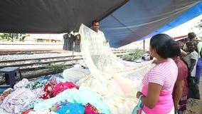 HIKKADUWA, SRI LANKA - FEBRUAR 2014: Lokaler Verkäufer, der Gewebe an Hikkaduwa-Markt zeigt und vereinbart Markt Hikkaduwa Sonnta stock footage