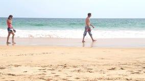 HIKKADUWA, SRI LANKA - FEBRUAR 2014: Mann und Frau, die vor Kamera mit Wellen im Hintergrund überschreiten stock video