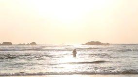 HIKKADUWA, SRI LANKA - FEBRUAR 2014: Meerblick in Hikkaduwa im Sonnenuntergang mit den Wellen, die den Strand und die Leute baden stock video