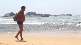 HIKKADUWA, SRI LANKA - FEBRUAR 2014: Meerblick in Hikkaduwa mit den Wellen, die den Strand spritzen, während ein alter Mann vorbe stock video footage
