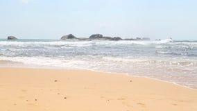 HIKKADUWA, SRI LANKA - FEBRUAR 2014: Meerblick in Hikkaduwa mit den Wellen, die den Strand spritzen, während Leute vorbei übersch stock video footage