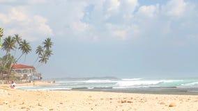HIKKADUWA, SRI LANKA - FEBRUAR 2014: Meerblick in Hikkaduwa mit den Wellen, die den Strand spritzen, während Leute vorbei übersch stock video