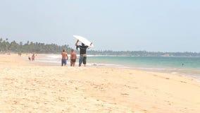 HIKKADUWA, SRI LANKA - FEBRUARI 2014: De mens draagt surfplank op zijn hoofd terwijl het lopen op zandig strand stock videobeelden