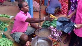 HIKKADUWA SRI LANKA - FEBRUARI 2014: Lokal man som väger livsmedel på den Hikkaduwa marknaden Den Hikkaduwa söndag marknaden är b arkivfilmer