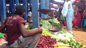 HIKKADUWA SRI LANKA - FEBRUARI 2014: Lokal man som väger livsmedel på den Hikkaduwa marknaden Den Hikkaduwa söndag marknaden är b stock video