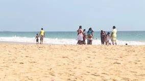 HIKKADUWA SRI LANKA - FEBRUARI 2014: Lokaler som tycker om stranden och spelar i bränningen Vågor är mycket starka och inte många lager videofilmer