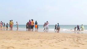 HIKKADUWA SRI LANKA - FEBRUARI 2014: Lokaler som tycker om stranden och spelar i bränningen Vågor är mycket starka och inte många arkivfilmer
