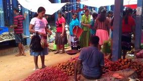 HIKKADUWA SRI LANKA - FEBRUARI 2014: Man som säljer livsmedel till kvinnan på den Hikkaduwa marknaden Den Hikkaduwa söndag markna lager videofilmer