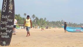 HIKKADUWA SRI LANKA - FEBRUARI 2014: Sikt av den Hikkaduwa stranden, medan lokaler går på stranden Hikkaduwa är berömd för dess b arkivfilmer