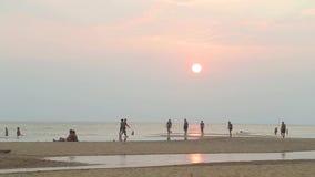 HIKKADUWA SRI LANKA - FEBRUARI 2014: Sikt av den Hikkaduwa stranden på solnedgången, medan folket tycker om aftonljus- och kylare stock video