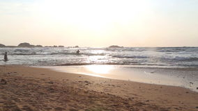 HIKKADUWA, SRI LANKA - FEBRUARY 2014: Beach view in Hikkaduwa in sunset with waves splashing the beach and people getting in the o. Cean. Hikkaduwa is famous for stock video