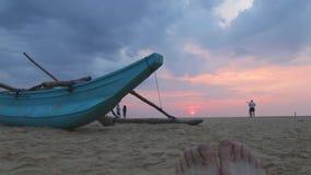 HIKKADUWA, SRI LANKA - FEBRUARY 2014: Boat on Hikkaduwa beach at sunset with people passing by. Hikkaduwa is famous for its beauti. Ful beaches stock video footage