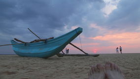 HIKKADUWA, SRI LANKA - FEBRUARY 2014: Boat on Hikkaduwa beach at sunset with people taking pictures. Hikkaduwa is famous for its b. Eautiful beaches stock video