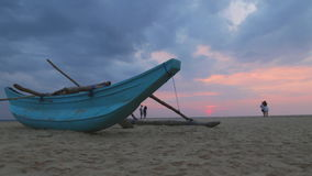 HIKKADUWA, SRI LANKA - FEBRUARY 2014: Boat on Hikkaduwa beach at sunset with people taking pictures. Hikkaduwa is famous for its b stock video footage