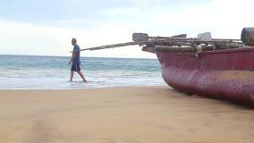 HIKKADUWA, SRI LANKA - FEBRUARY 2014: Boat on Hikkaduwa beach while waves are splashing and a man is passing by. Hikkaduwa is famo stock footage