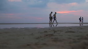 HIKKADUWA, SRI LANKA - FEBRUARY 2014: Family walking on beach and throwing child in the air. Hikkaduwa is famous for its beautiful stock video footage