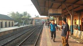 HIKKADUWA, SRI LANKA - FEBRUARY 2014: Local people waiting for train on Hikkaduwa train station as train arrives. The Sri Lankan r. Ailway transports millions of stock video