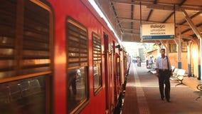 HIKKADUWA, SRI LANKA - FEBRUARY 2014: Local people walking on Hikkaduwa train station while train arrives. The Sri Lankan railway. Transports millions of people stock video