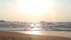 HIKKADUWA, SRI LANKA - FEBRUARY 2014: Tourist couple in silhouette walking on beach at sunset. stock footage