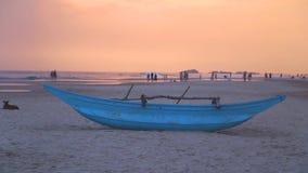 HIKKADUWA, SRI LANKA - FEBRUARY 2014: Traditional fishing boat on Hikkaduwa beach at sunset. Hikkaduwa is famous for its beautiful. Beaches stock video footage