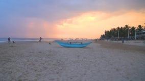 HIKKADUWA, SRI LANKA - FEBRUARY 2014: Traditional fishing boat on Hikkaduwa beach at sunset. Hikkaduwa is famous for its beautiful. Beaches stock footage
