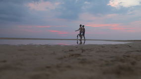 HIKKADUWA, SRI LANKA - FEBRUARY 2014: The view of couple passing by on beach in Hikkaduwa. Hikkaduwa is famous for its beautiful b. Eaches stock footage