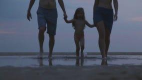 HIKKADUWA, SRI LANKA - FEBRUARY 2014: View of couple walking on beach with child following. Hikkaduwa is famous for its beautiful. Beaches stock video footage