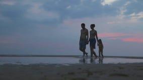 HIKKADUWA, SRI LANKA - FEBRUARY 2014: The View of Hikkaduwa beach at sunset with family of three passing by. Hikkaduwa is famous f. Or its beautiful beaches stock video footage