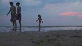HIKKADUWA, SRI LANKA - FEBRUARY 2014: The View of Hikkaduwa beach at sunset with family of three running by. Hikkaduwa is famous f. Or its beautiful beaches stock video