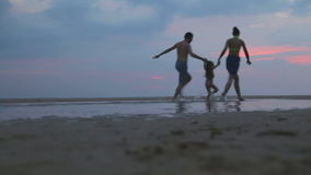 HIKKADUWA, SRI LANKA - FEBRUARY 2014: The View of Hikkaduwa beach at sunset with family of three running by. Hikkaduwa is famous f. Or its beautiful beaches stock video footage