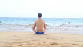 HIKKADUWA, SRI LANKA - FEBRUARY 2014: View of Hikkaduwa beach while waves are splashing and a man is meditating near the ocean. Hi stock video footage