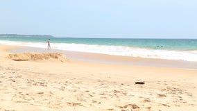 HIKKADUWA, SRI LANKA - FEBRUARY 2014: View of Hikkaduwa beach while waves are splashing and people are enjoying themselves in the  stock footage