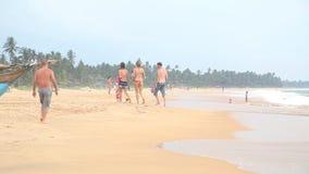 HIKKADUWA, SRI LANKA - FEBRUARY 2014: View of Hikkaduwa beach while waves are splashing and people are passing by the ocean. Hikka stock video footage