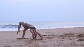 HIKKADUWA, SRI LANKA - MÄRZ 2014: Die Ansicht einer Frau, die heraus auf den Strand in Hikkaduwa ausdehnt Hikkaduwa ist für seine stock footage
