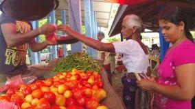 HIKKADUWA, SRI LANKA - MÄRZ 2014: Frau, die frische Früchte auf dem Markt Sri Lankan vom lokalen Verkäufer kauft stock video footage