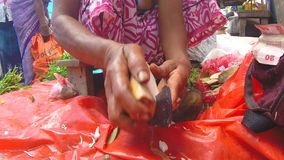 HIKKADUWA, SRI LANKA - MÄRZ 2014: Frau, die Gemüse mit scharfem Messer an Sonntags-Markt schneidet stock footage