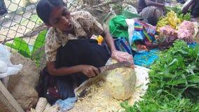 HIKKADUWA, SRI LANKA - MÄRZ 2014: Frauenausschnitt Durianfrucht mit großem Messer an Sonntags-Markt stock footage