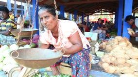 HIKKADUWA, SRI LANKA - MÄRZ 2014: Lokale Frau, die vor seiner Repartierung an Markt Hikkaduwa Sonntag, bekannt für sein wid sitzt stock video footage