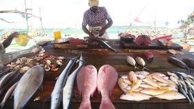 HIKKADUWA, SRI LANKA - MÄRZ 2014: Lokale Mannausschnittfische an Markt Hikkaduwa Sonntag, bekannt für seine breite Palette von fr stock video footage