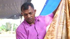 HIKKADUWA, SRI LANKA - MÄRZ 2014: Lokaler Mann, der Gewebe an Markt Hikkaduwa Sonntag, bekannt für seine breite Palette von frisc stock video