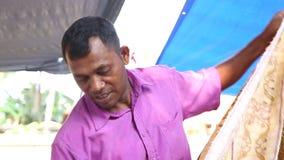 HIKKADUWA, SRI LANKA - MÄRZ 2014: Lokaler Mann, der Gewebe an Markt Hikkaduwa Sonntag, bekannt für seine breite Palette von frisc stock video footage