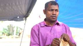 HIKKADUWA, SRI LANKA - MÄRZ 2014: Lokaler Mann, der Gewebe an Markt Hikkaduwa Sonntag, bekannt für seine breite Palette von frisc stock footage