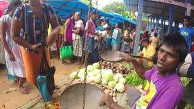 HIKKADUWA, SRI LANKA - MÄRZ 2014: Lokaler Mann, der sein Erzeugnis wiegt und zur Kamera auf den Markt, bekannt nach seiner breite stock video footage