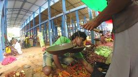 HIKKADUWA, SRI LANKA - MÄRZ 2014: Lokaler Mann, der seins Erzeugnis am Markt, bekannt für seine breite Palette von frischem und v stock video footage