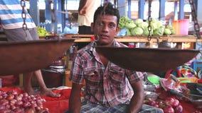 HIKKADUWA, SRI LANKA - MÄRZ 2014: Lokaler Mann, der seins Erzeugnis an Markt Hikkaduwa Sonntag, bekannt für seine breite Palette  stock footage