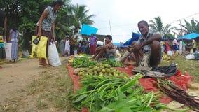 HIKKADUWA, SRI LANKA - MÄRZ 2014: Lokaler Mann, der am Sonntags-Markt sitzt und verkauft Märkte Sri Lankan bekannt für sein breit stock footage