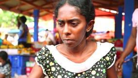 HIKKADUWA, SRI LANKA - MÄRZ 2014: Porträt einer lokalen jungen Frau, die an Markt Hikkaduwa Sonntag, bekannt für seine breite Pal stock footage
